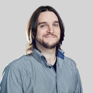 person with medium length hair and facial hair smiling