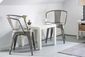 a small white end table surrounded by two silver chairs