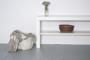white table and shelf unit next to a basket holding cloth materials