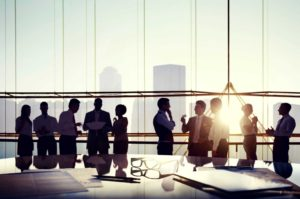 Ten employees having various conversations in front of a wall of glass with sunset