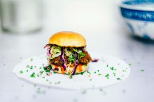 a small burger with purple and green garnish