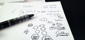 a pen and blank white paper covered in design doodles