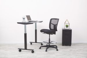 an adjustable standing desk with adjustable chair and small movable cabinet